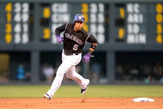 Aug 6, 2014; Denver, CO, USA; Colorado Rockies left fielder Carlos Gonzalez (5) rounds second on his way to score in the fourth inning against the Chicago Cubs at Coors Field. Mandatory Credit: Ron Chenoy-USA TODAY Sports