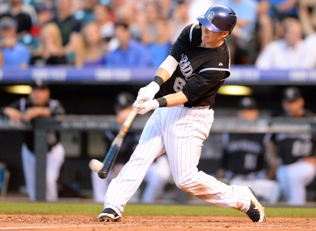 Aug 6, 2014; Denver, CO, USA; Colorado Rockies left fielder Corey Dickerson (6) hits a RBI triple in the fourth inning against the Chicago Cubs at Coors Field. Mandatory Credit: Ron Chenoy-USA TODAY Sports