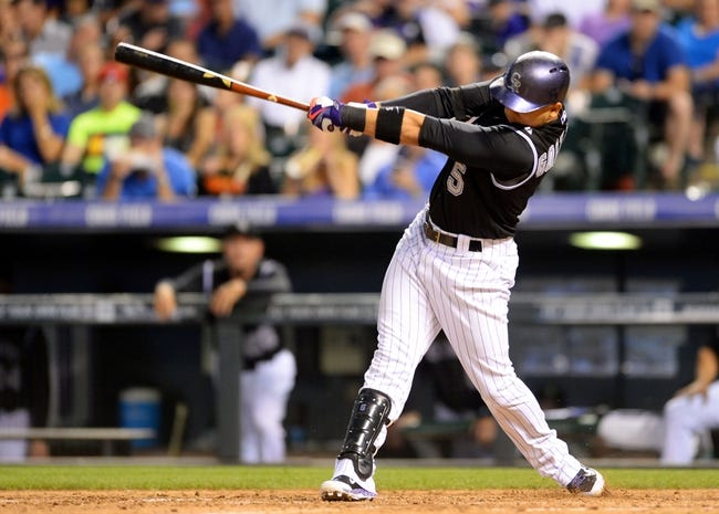 Aug 6, 2014; Denver, CO, USA; Colorado Rockies left fielder Carlos Gonzalez (5) hits a two run home run in the sixth inning against the Chicago Cubs at Coors Field. Mandatory Credit: Ron Chenoy-USA TODAY Sports