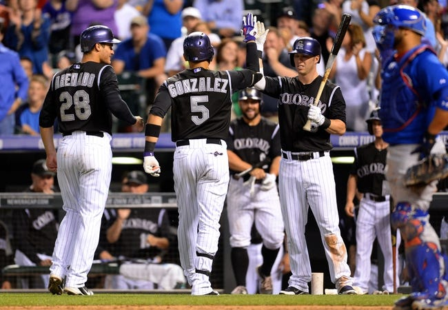 Aug 6, 2014; Denver, CO, USA; Colorado Rockies left fielder Carlos Gonzalez (5)  by third baseman Nolan Arenado (28) and left fielder Corey Dickerson (6) for his two run home run in the sixth inning against the Chicago Cubs at Coors Field. Mandatory Credit: Ron Chenoy-USA TODAY Sports