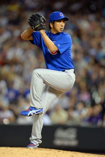 Aug 6, 2014; Denver, CO, USA; Chicago Cubs relief pitcher Kyuji Fujikawa (11) delivers a pitch in the sixth inning against the Colorado Rockies at Coors Field. Mandatory Credit: Ron Chenoy-USA TODAY Sports