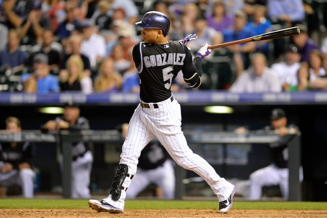 Aug 6, 2014; Denver, CO, USA; Colorado Rockies left fielder Carlos Gonzalez (5) hits a double in the seventh inning against the Chicago Cubs at Coors Field. Mandatory Credit: Ron Chenoy-USA TODAY Sports