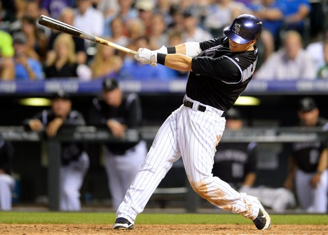 Aug 6, 2014; Denver, CO, USA; Colorado Rockies left fielder Corey Dickerson (6) hits a two run RBI single in the seventh inning against the Colorado Rockies at Coors Field. Mandatory Credit: Ron Chenoy-USA TODAY Sports
