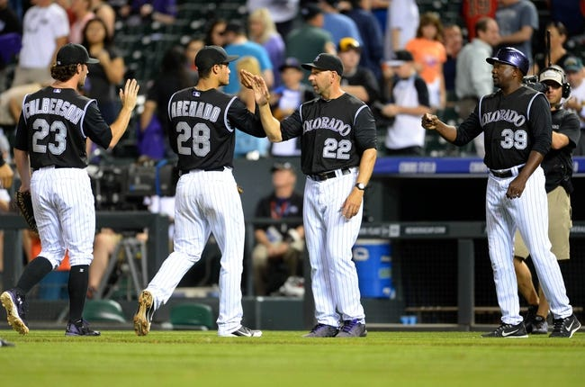 Aug 6, 2014; Denver, CO, USA; Colorado Rockies third baseman Charlie Culberson (23) and third baseman Nolan Arenado (28) and manager Walt Weiss (22) and third base coach Stu Cole (39) celebrate the win over the Chicago Cubs at Coors Field. The Rockies defeated the Cubs 13-4. Mandatory Credit: Ron Chenoy-USA TODAY Sports