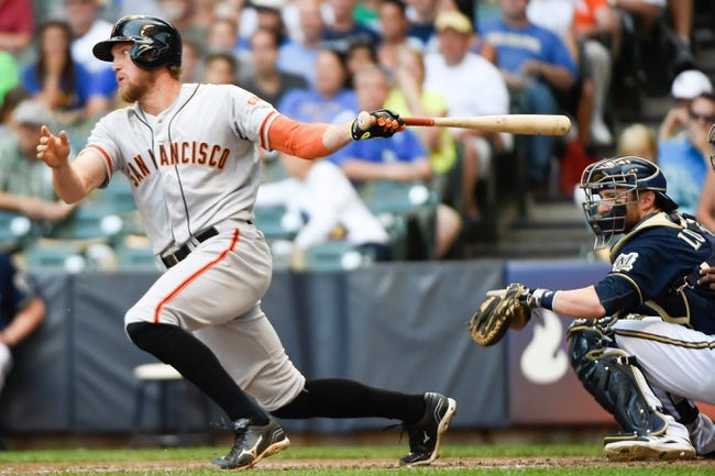 Aug 7, 2014; Milwaukee, WI, USA;  San Francisco Giants right fielder Hunter Pence (8) hits a single to drive in a run as Milwaukee Brewers catcher Jonathan Lucroy (20) watches in the fifth inning at Miller Park. Mandatory Credit: Benny Sieu-USA TODAY Sports