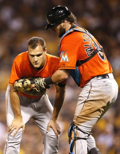 Aug 7, 2014; Pittsburgh, PA, USA; Miami Marlins relief pitcher Dan Jennings (left) is assisted by catcher Jarrod Saltalamacchia (right) after Jennings was hit in the head by a line drive from the bat of Pittsburgh Pirates shortstop Jordy Mercer (not pictured) during the seventh inning at PNC Park. Mandatory Credit: Charles LeClaire-USA TODAY Sports