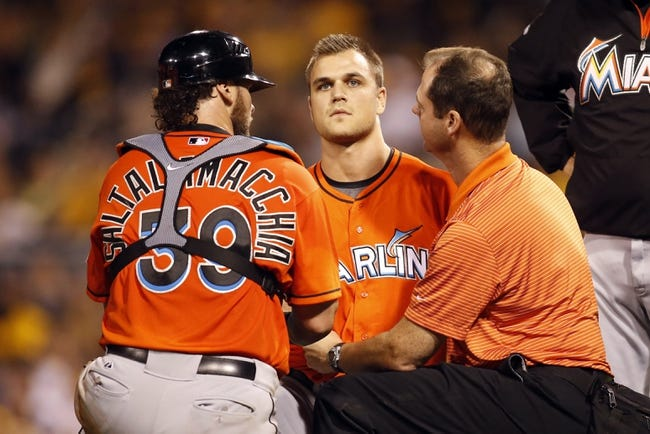 Aug 7, 2014; Pittsburgh, PA, USA; Miami Marlins relief pitcher Dan Jennings (middle) is assisted by catcher Jarrod Saltalamacchia (left) and Marlins trainer Sean Cunningham (right) after Jennings was hit in the head by a line drive from the bat of Pittsburgh Pirates shortstop Jordy Mercer (not pictured) during the seventh inning at PNC Park. Mandatory Credit: Charles LeClaire-USA TODAY Sports