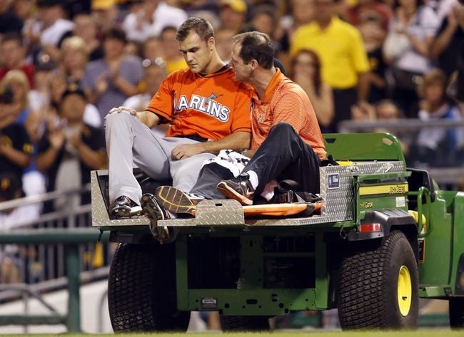 Aug 7, 2014; Pittsburgh, PA, USA; Miami Marlins relief pitcher Dan Jennings (left) is taken from the field along with Miami trainer Sean Cunningham (right) after Jennings was hit in the head by a line drive from the bat of Pittsburgh Pirates shortstop Jordy Mercer (not pictured) during the seventh inning at PNC Park. Mandatory Credit: Charles LeClaire-USA TODAY Sports