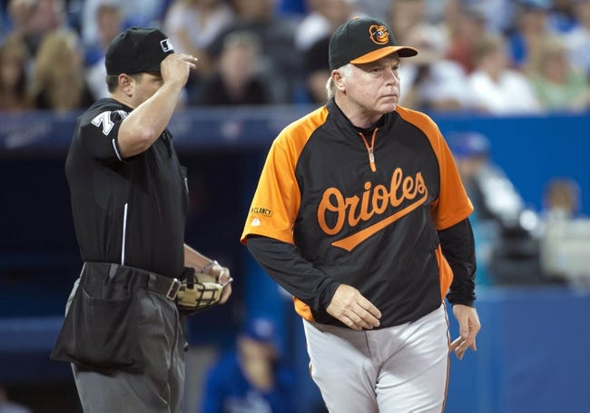 Aug 7, 2014; Toronto, Ontario, CAN; Baltimore Orioles manager Buck Showalter (26) leaves the field after talking with home plate umpire D.J. Reyburn (70) during the eighth inning in a game against the Toronto Blue Jays at Rogers Centre. The Baltimore Orioles won 2-1. Mandatory Credit: Nick Turchiaro-USA TODAY Sports