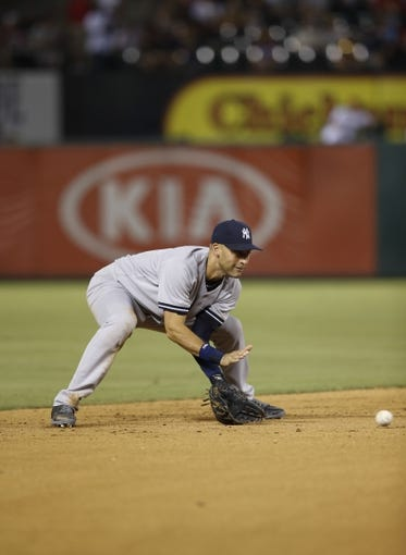 Jul 28, 2014; Arlington, TX, USA; New York Yankees shortstop Derek Jeter (2) fields a ground ball during the game against the Texas Rangers at Globe Life Park in Arlington. Mandatory Credit: Kevin Jairaj-USA TODAY Sports