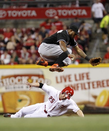 Aug 8, 2014; Cincinnati, OH, USA; Cincinnati Reds left fielder Skip Schumaker (25) breaks up a double play during the seventh inning against the Miami Marlins second baseman Jordany Valdespin (1) at Great American Ball Park. The Marlins won 2-1. Mandatory Credit: Frank Victores-USA TODAY Sports