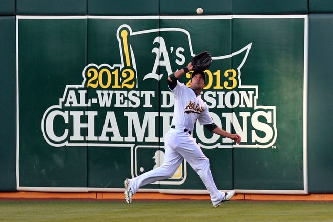 Aug 8, 2014; Oakland, CA, USA; Oakland Athletics center fielder Sam Fuld (29) runs down Minnesota Twins catcher Kurt Suzuki (not pictured) deep fly ball in the second inning to retire the side of their MLB baseball game at O.co Coliseum. Mandatory Credit: Lance Iversen-USA TODAY Sports