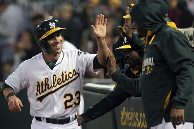 Aug 8, 2014; Oakland, CA, USA; Oakland Athletics center fielder Sam Fuld (23) celebrates with teammates in the dugout after scoring one of three runs on a Coco Crisp (4) triple in the fifth inning against the Minnesota Twins at O.co Coliseum. Mandatory Credit: Lance Iversen-USA TODAY Sports