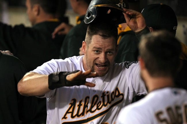 Aug 8, 2014; Oakland, CA, USA; Oakland Athletics first baseman Stephen Vogt (21) celebrates with teammates in the dugout after scoring one of three runs on a Coco Crisp (4) triple in the fifth inning against the Minnesota Twins at O.co Coliseum. Mandatory Credit: Lance Iversen-USA TODAY Sports