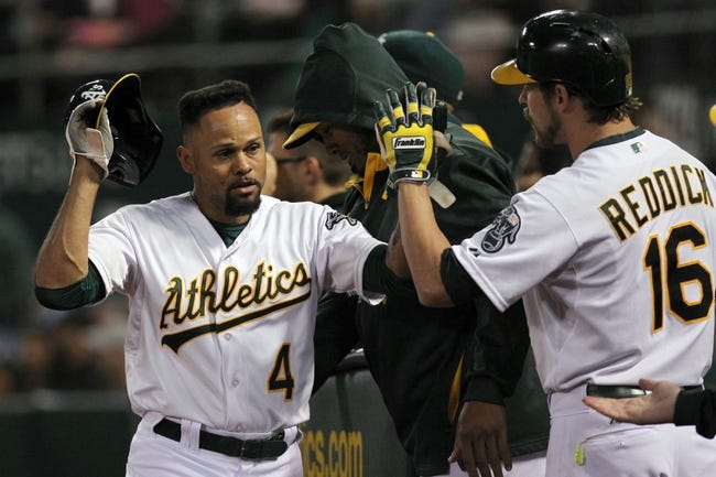 Aug 8, 2014; Oakland, CA, USA; Oakland Athletics DH Coco Crisp (4) celebrates with teammates in the dugout after scoring from third base on a wild pitch in the fifth inning against the Minnesota Twins at O.co Coliseum. Mandatory Credit: Lance Iversen-USA TODAY Sports