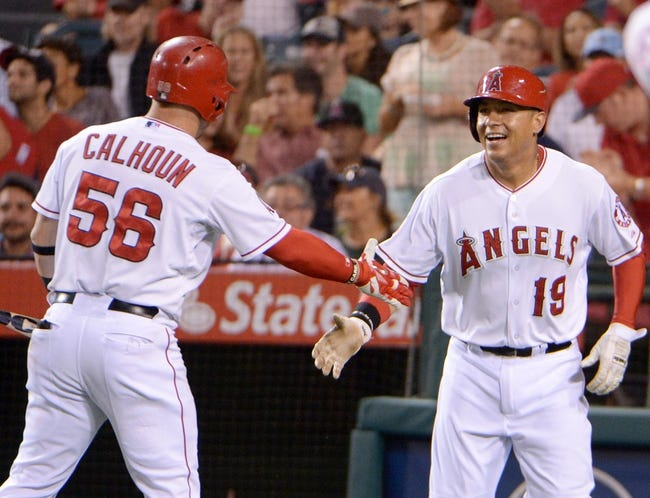 Aug 8, 2014; Anaheim, CA, USA; Los Angeles Angels designated hitter Efren Navarro (19) celebrates with right fielder Kole Calhoun (56) after scoring in the third inning against the Boston Red Sox at Angel Stadium of Anaheim. Mandatory Credit: Kirby Lee-USA TODAY Sports