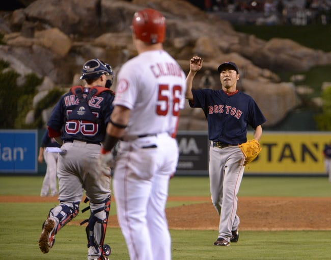 Aug 8, 2014; Anaheim, CA, USA; Boston Red Sox reliever Koji Uehara (19) celebrates with catcher Christian Vazquez (55) after striking out Los Angeles Angels right fielder Kole Calhoun (56) for the final out at Angel Stadium of Anaheim. The Red Sox won 4-2. Mandatory Credit: Kirby Lee-USA TODAY Sports