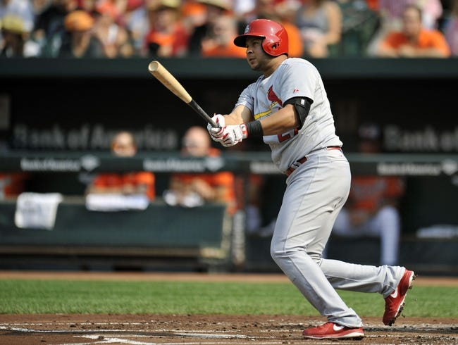 Aug 9, 2014; Baltimore, MD, USA; St. Louis Cardinals designated hitter Jhonny Peralta (27) hits a RBI double in the first inning against the Baltimore Orioles at Oriole Park at Camden Yards. Mandatory Credit: Joy R. Absalon-USA TODAY Sports