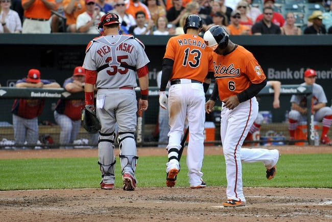 Aug 9, 2014; Baltimore, MD, USA; Baltimore Orioles second baseman Jonathan Schoop (6) scores on a wild pitch by St. Louis Cardinals pitcher Kevin Siegrist (not shown) in the eighth inning at Oriole Park at Camden Yards. The Orioles defeated the Cardinals 10-3. Mandatory Credit: Joy R. Absalon-USA TODAY Sports