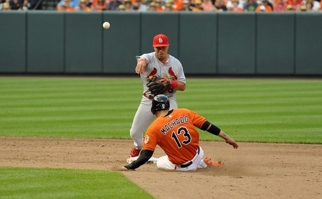 Aug 9, 2014; Baltimore, MD, USA; Baltimore Orioles third baseman Manny Machado (13) is out at second base as St. Louis Cardinals second baseman Kolten Wong (16) starts the double play in the sixth inning at Oriole Park at Camden Yards. The Orioles defeated the Cardinals 10-3. Mandatory Credit: Joy R. Absalon-USA TODAY Sports