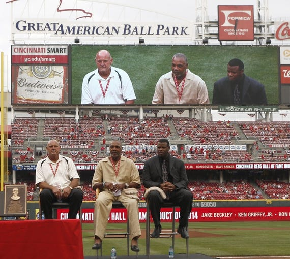 Aug 9, 2014; Cincinnati, OH, USA; Cincinnati Reds former second baseman Ron Oester (left) , right fielder Dave Parker (middle) and center fielder Ken Griffey, Jr. (right) sit on the field as they were inducted into the Reds Hall of Fame before a game between the Miami Marlins and the Cincinnati Reds at Great American Ball Park. Mandatory Credit: David Kohl-USA TODAY