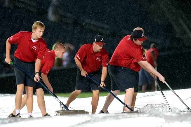 Aug 9, 2014; Atlanta, GA, USA; Atlanta Braves grounds crew members work on removing water from the infield tarp during a rain delay prior to game the between the Washington Nationals and the Atlanta Braves at Turner Field. Mandatory Credit: Dale Zanine-USA TODAY Sports