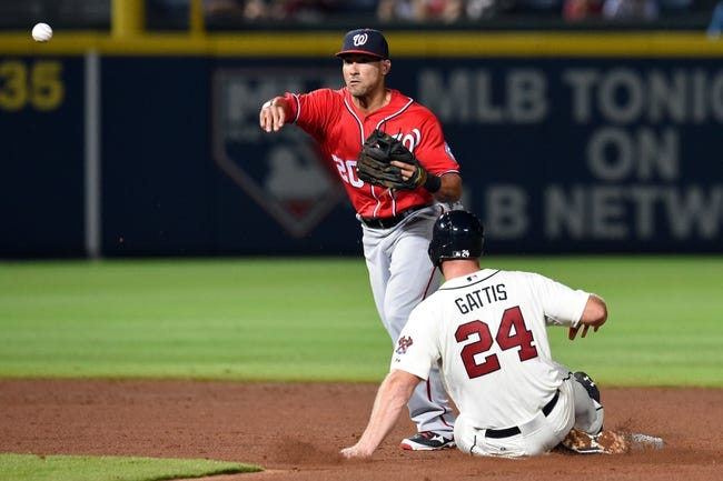Aug 9, 2014; Atlanta, GA, USA; Washington Nationals shortstop Ian Desmond (20) turns a double play over Atlanta Braves catcher Evan Gattis (24) during the second inning at Turner Field. Mandatory Credit: Dale Zanine-USA TODAY Sports