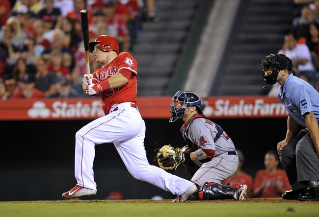 August 9, 2014; Anaheim, CA, USA; Los Angeles Angels designated hitter Mike Trout (27) hits a solo home run in the eighth inning against the Boston Red Sox at Angel Stadium of Anaheim. Mandatory Credit: Gary A. Vasquez-USA TODAY Sports