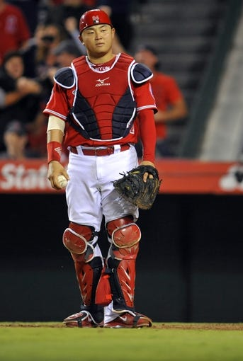 August 9, 2014; Anaheim, CA, USA; Los Angeles Angels catcher  Hank Conger (24) reacts after Boston Red Sox second baseman Dustin Pedroia (15) scores a run in the fourteenth inning at Angel Stadium of Anaheim. Mandatory Credit: Gary A. Vasquez-USA TODAY Sports