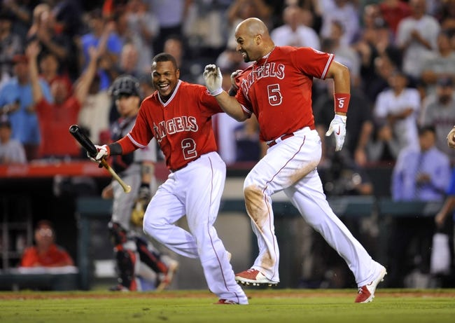 August 9, 2014; Anaheim, CA, USA; Los Angeles Angels first baseman Albert Pujols (5) celebrates with shortstop Erick Aybar (2) after he hits a solo home run in the nineteenth inning against the Boston Red Sox at Angel Stadium of Anaheim. Mandatory Credit: Gary A. Vasquez-USA TODAY Sports