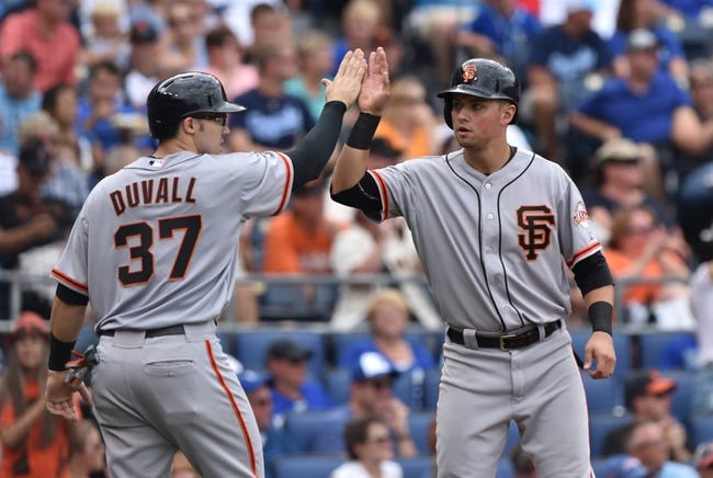 Aug 10, 2014; Kansas City, MO, USA; San Francisco Giants players Joe Panik (right) and Adam Duvall (37) celebrate after scoring against the Kansas City Royals during the seventh inning at Kauffman Stadium. Kansas City defeated San Francisco 7-4. Mandatory Credit: Peter G. Aiken-USA TODAY Sports