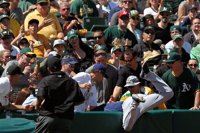 Aug 10, 2014; Oakland, CA, USA; Minnesota Twins third baseman Eduardo Nunez (9) falls into the third base side seats after catching a Oakland Athletics catcher John Jaso (not pictured) foul ball in the seventh inning at O.co Coliseum. Twins won 6-1. Mandatory Credit: Lance Iversen-USA TODAY Sports.