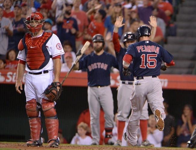 Aug 8, 2014; Anaheim, CA, USA; Boston Red Sox second baseman Dustin Pedroia (15) is greeted by catcher Mike Napoli and center fielder Brock Holt (26) after scoring in the third inning as Los Angeles Angels catcher Chris Iannetta (right) watches at Angel Stadium of Anaheim. Mandatory Credit: Kirby Lee-USA TODAY Sports