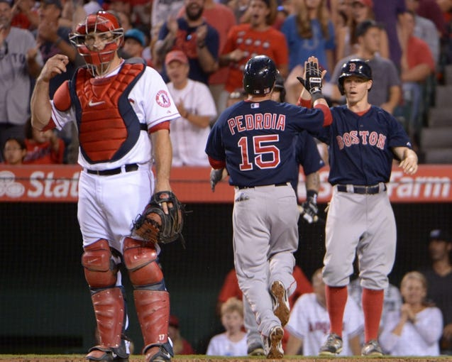 Aug 8, 2014; Anaheim, CA, USA; Boston Red Sox second baseman Dustin Pedroia (15) is greeted by center fielder Brock Holt (26) after scoring in the third inning as Los Angeles Angels catcher Chris Iannetta (right) watches at Angel Stadium of Anaheim. Mandatory Credit: Kirby Lee-USA TODAY Sports