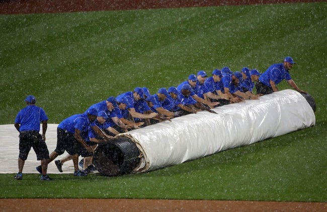 Aug 12, 2014; New York, NY, USA; The Citi Field grounds crew unrolls the tarp as it rains during the third inning of the game between the New York Mets and the Washington Nationals. Mandatory Credit: Anthony Gruppuso-USA TODAY Sports
