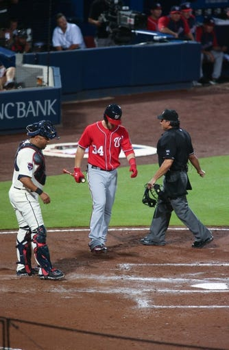 Aug 10, 2014; Atlanta, GA, USA; Washington Nationals left fielder Bryce Harper (34) walks to the plate for an at bat as Atlanta Braves catcher Gerald Laird (11) and home plate umpire Phil Cuzzi are shown in the second inning of their game at Turner Field. The Braves won 3-1. Mandatory Credit: Jason Getz-USA TODAY Sports