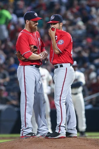 Aug 10, 2014; Atlanta, GA, USA; Washington Nationals starting pitcher Gio Gonzalez (47) talks with Washington Nationals first baseman Adam LaRoche (25) during their game against the Atlanta Braves at Turner Field. The Braves won 3-1. Mandatory Credit: Jason Getz-USA TODAY Sports