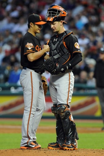 Aug 15, 2014; Cleveland, OH, USA; Baltimore Orioles starting pitcher Wei-Yin Chen (16) talks with catcher Caleb Joseph (36) after Cleveland Indians designated hitter Zach Walters (not pictured) hit a home run during the fifth inning at Progressive Field. Mandatory Credit: Ken Blaze-USA TODAY Sports