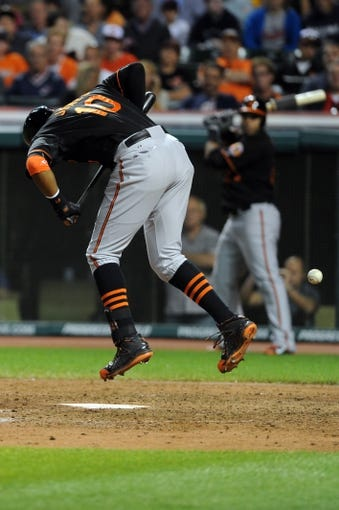 Aug 15, 2014; Cleveland, OH, USA; Baltimore Orioles center fielder Adam Jones (10) leaps after attempting to bunt during the eighth inning against the Cleveland Indians at Progressive Field. Mandatory Credit: Ken Blaze-USA TODAY Sports