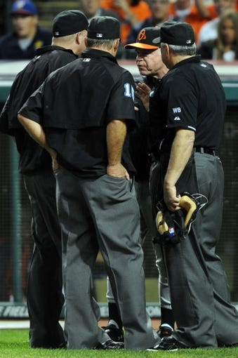 Aug 15, 2014; Cleveland, OH, USA; Baltimore Orioles manager Buck Showalter (26) argues with the umpire crew as to whether Baltimore Orioles center fielder Adam Jones (not pictured) was hit by a pitch or not during the eighth inning against the Cleveland Indians at Progressive Field. Mandatory Credit: Ken Blaze-USA TODAY Sports