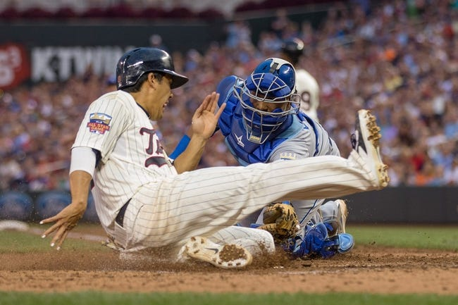 Aug 16, 2014; Minneapolis, MN, USA; Minnesota Twins catcher Kurt Suzuki (8) slides safely into home plate before Kansas City Royals catcher Salvador Perez (13) can make a tag in the seventh inning at Target Field. Mandatory Credit: Jesse Johnson-USA TODAY Sports