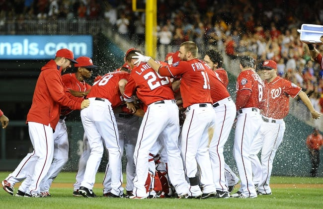 Aug 16, 2014; Washington, DC, USA; Washington Nationals players mob catcher Wilson Ramos (40) after his walk off RBI double during the ninth inning against the Pittsburgh Pirates at Nationals Park. The Nationals won 4-3. Mandatory Credit: Brad Mills-USA TODAY Sports