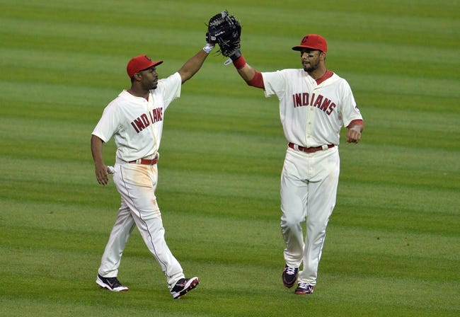 Aug 16, 2014; Cleveland, OH, USA; Cleveland Indians center fielder Michael Bourn (left) and right fielder Chris Dickerson (38) celebrate a 6-0 win over the Baltimore Orioles at Progressive Field. Mandatory Credit: David Richard-USA TODAY Sports