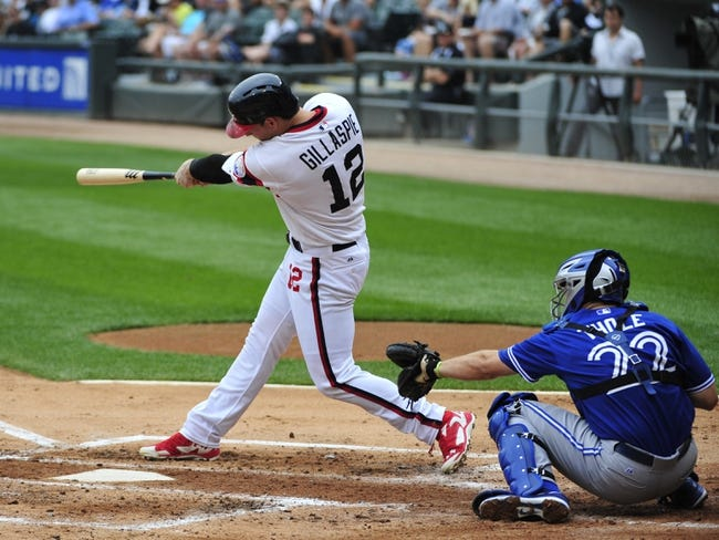 Aug 17, 2014; Chicago, IL, USA; Chicago White Sox third baseman Conor Gillaspie (12) hits a grand slam home against the Toronto Blue Jays during the first inning at U.S Cellular Field. Mandatory Credit: David Banks-USA TODAY Sports