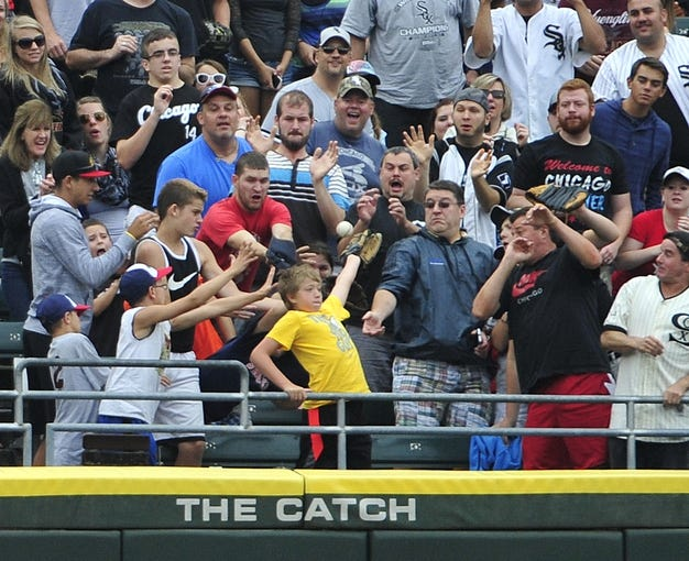 Aug 17, 2014; Chicago, IL, USA; Fans try to catch Chicago White Sox center fielder Jordan Danks (not pictured) two-run homer against the Toronto Blue Jays during the first inning at U.S Cellular Field. Mandatory Credit: David Banks-USA TODAY Sports