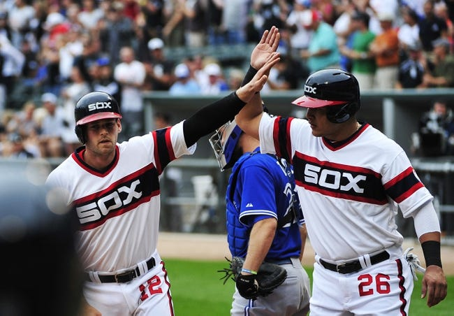 Aug 17, 2014; Chicago, IL, USA; Chicago White Sox third baseman Conor Gillaspie (12) is greeted by right fielder Avisail Garcia (26) after  hitting a grand slam home against the Toronto Blue Jays during the first inning at U.S Cellular Field. Mandatory Credit: David Banks-USA TODAY Sports