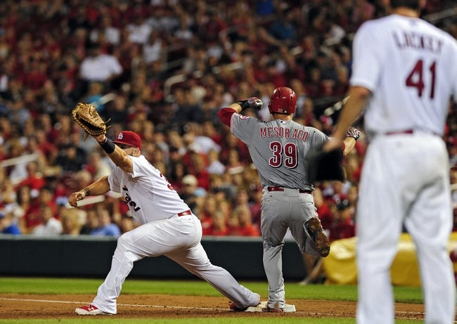 Aug 19, 2014; St. Louis, MO, USA; Cincinnati Reds catcher Devin Mesoraco (39) beats the throw to St. Louis Cardinals first baseman Matt Adams (32) as starting pitcher John Lackey (41) looks on during the sixth inning at Busch Stadium. Mandatory Credit: Jeff Curry-USA TODAY Sports