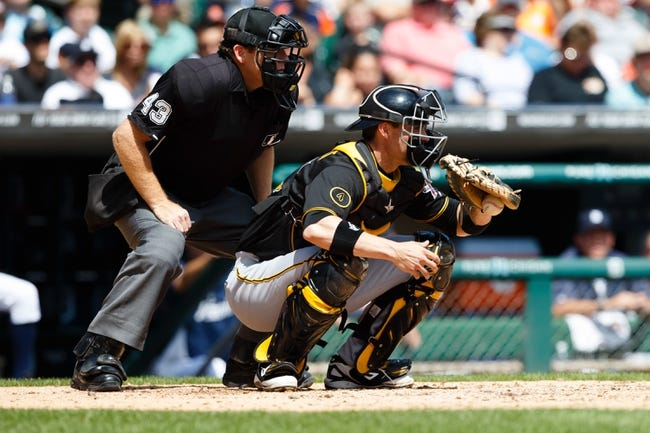 Aug 14, 2014; Detroit, MI, USA; Pittsburgh Pirates catcher Chris Stewart (19) catches in front of umpire Paul Schrieber (43) against the Detroit Tigers at Comerica Park. Mandatory Credit: Rick Osentoski-USA TODAY Sports