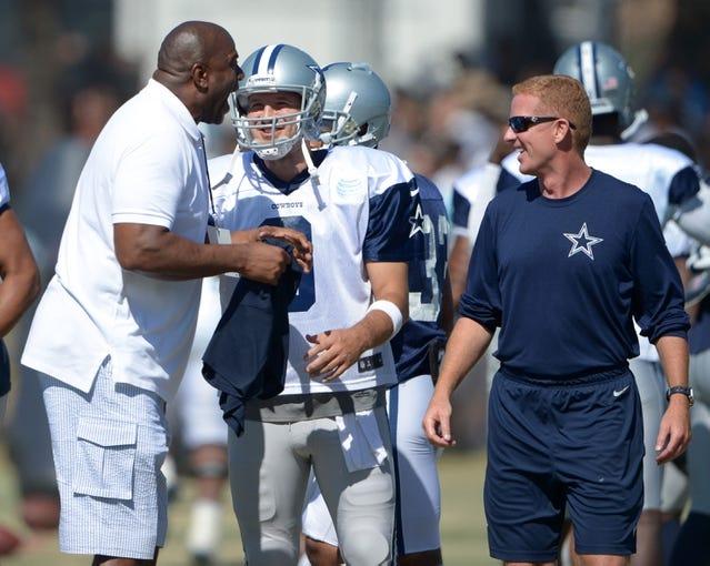 Aug 12, 2014; Oxnard, CA, USA; Magic Johnson (left) talks with Dallas Cowboys quarterback Tony Romo (9) and coach Jason Garrett (right) at scrimmage against the Oakland Raiders at River Ridge Fields. Mandatory Credit: Kirby Lee-USA TODAY Sports