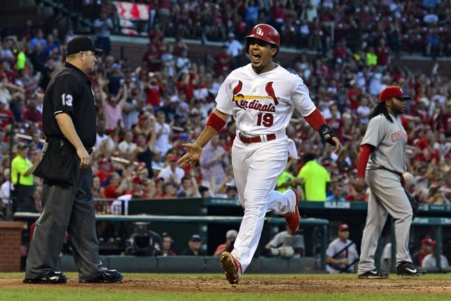 Aug 20, 2014; St. Louis, MO, USA; St. Louis Cardinals center fielder Jon Jay (19) celebrates after scoring as Cincinnati Reds starting pitcher Johnny Cueto (47) looks on during the third inning at Busch Stadium. Mandatory Credit: Jeff Curry-USA TODAY Sports